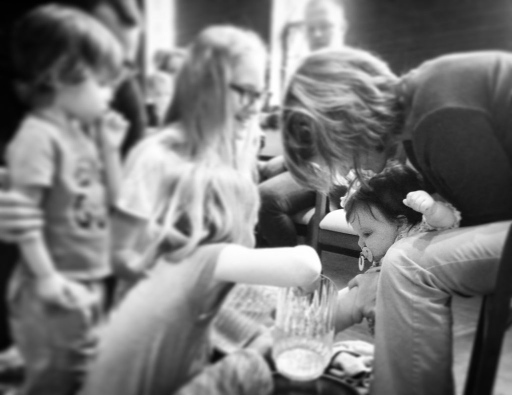 Poppy at her first Maundy Thursday service, her sisters washing her feet.